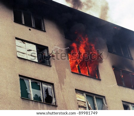 SARAJEVO, BOSNIA - MAR 18: A man attempts to put out a fire in a neighboring apartment during the final days of siege in Sarajevo, Bosnia, on Monday, March 18, 1996