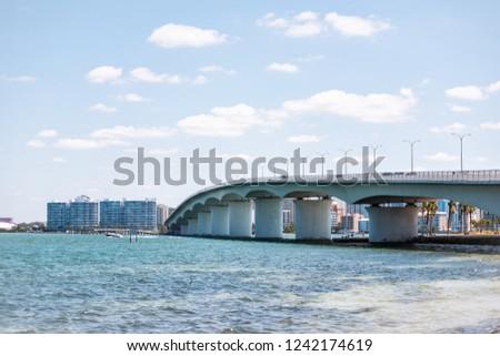 Sarasota, USA Beach in Florida city during sunny day, cityscape, bay, buildings, and John Ringling causeway bridge #1242174619