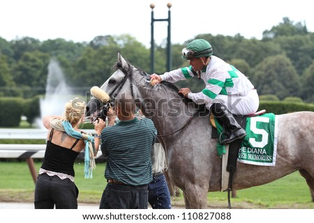 SARATOGA SPRINGS, NY - JULY 28: Jockey Javier Castellano aboard Winter Memories gets a cool sponge of water after winning The Diana Stakes on July 28, 2012 Saratoga Springs, New York