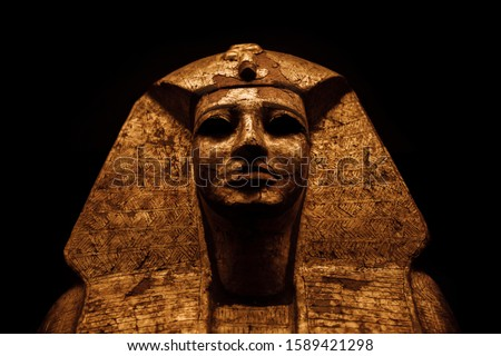 Sarcophagus of an ancient Egyptian mummy covered in solid gold with the black background. Stock photo ©