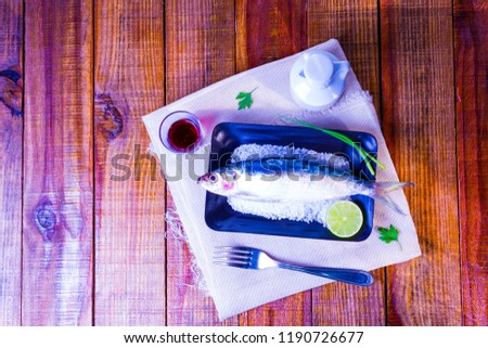 Sardine on the black dish chives olive oil noble salt salty tasty wine red wine delicious