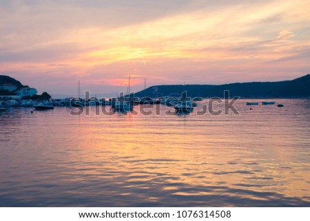Sardinia, Italy - August 8, 2015: The fiery sunset reflects on the sea of a small marina. #1076314508