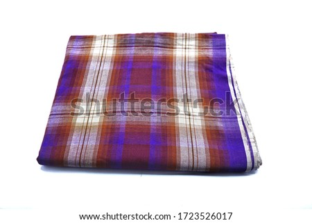 Sarong folded over a white background. Sarong is widely used by Muslims in performing their prayers.