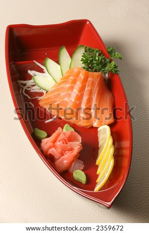 Sashimi. Boat-plate with salmon, ginger, cucumber and lemon