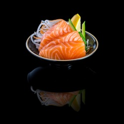 sashimi with salmon in a black plate. On a black background with reflection.