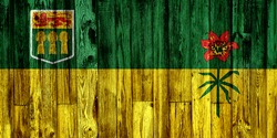 Saskatchewan flag painted on wooden background, closeup.