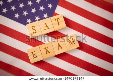 SAT Exam in Wooden block letters on US flag Stok fotoğraf ©