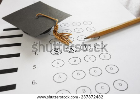 SAT test with pencil and mortar board graduation cap