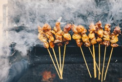 Satay goat satay, lamb, lamb or meat goat satay in grilling place with smoke by people with yummy looking. traditional satay from java, Indonesia.