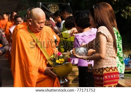 Satchanalai District. Sukhothai, THAILAND - APRIL 13: Thai people celebrate Songkran festival (water festival) in Satchanalai District. Sukhothai, Thailand on April 13, 2011. Offer food to monks.