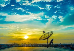 satelite dishes with sunset and city background