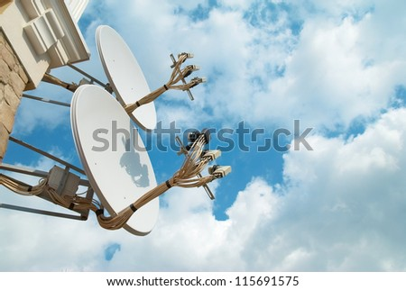 Satellite antenna on the wall with blue sky