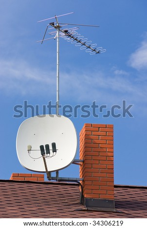 Satellite antenna, TV antenna and chimney on roof