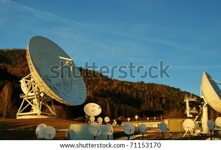 Satellite broadcasting dish at sunset time with mountains in background.