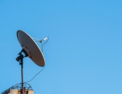 Satellite dish or parabolic antenna on the roof of a building against blue sky.