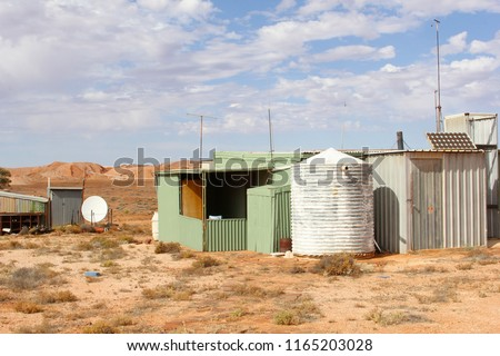 Satellite dish, solar energy panels on roof and water storage tank in desert village, Africa #1165203028