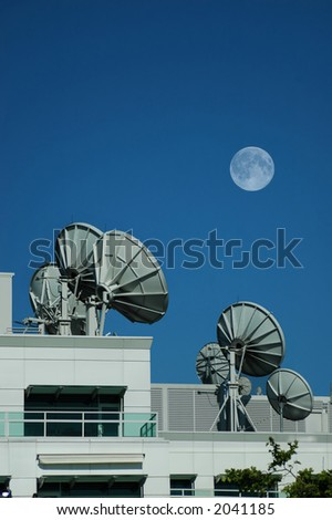 Satellite dishes in blue sky background with moon