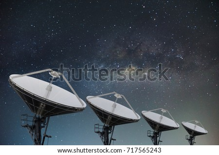 Satellite dishes on building for telecommunication with milky way sky background