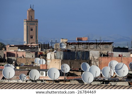 Satellite dishes on roofs in Marrakesh, Morocco. At background a mosque and the High Atlas mountains