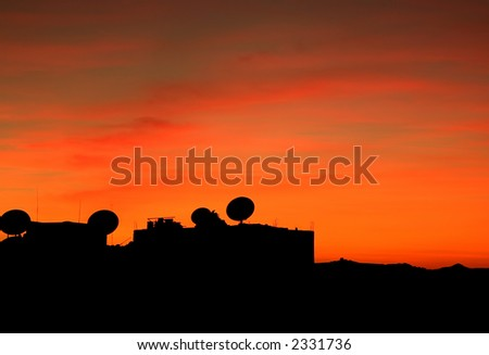Satellite Dishes silhouetted against the dusk sky.