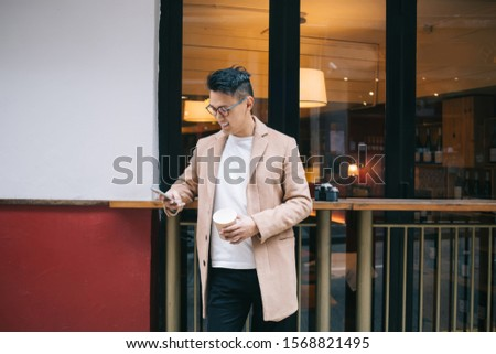 Satisfied Asian male journalist having rest while leaning on barrier and drinking coffee while texting with friends on mobile phone at city street #1568821495