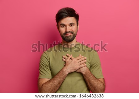 Satisfied bearded smiling man makes gratitude gesture, presses hands to heart, being thankful for help and support, appreciates someones care, wears casual t shirt, poses against pink background Сток-фото ©