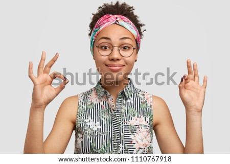 Satisfied beautiful African American female gestures indoor, shows okay sign, has pleasant smile, dressed in summer clothes, wears round glasses, isolated on white background. Ethnicity, body language