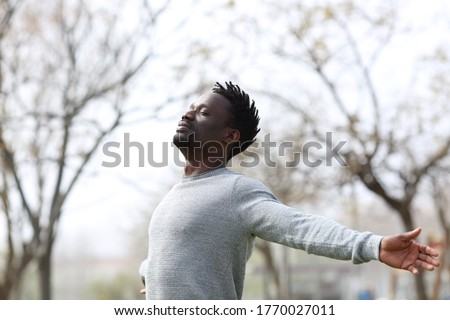Satisfied black man breathing fresh air with eyes closed standing in the park outdoors