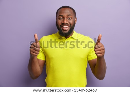 Satisfied black man gestures with both hands, shows approval gesture, keeps two thumbs raised, smiles broadly, wears yellow casual t shirt, stands against purple background. Thats nice, I like it #1340962469