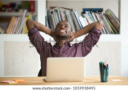 Satisfied black worker relaxing leaning in comfortable chair with hands overhead happy with finished work, successful business report and promising results. Concept of rewarding, resting and winning #1059938495