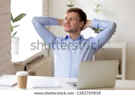 Satisfied businessman relaxing leaning back with hands behind head, enjoying break at workplace, happy man thinking about successful business project, strategy, finish work with laptop, dreaming #1282769818
