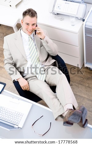 Satisfied businessman sitting by desk at office and calling on phone, feet on table, smiling, looking up at camera. High-angle view.
