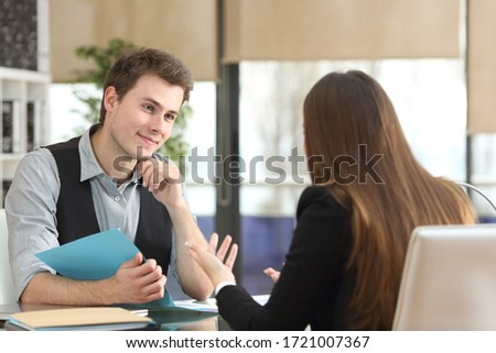 Satisfied businesspeople talking during an interview sitting at office