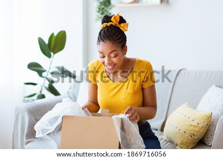 Satisfied Buyer. Portrait of curious cheerful black woman received package, unpacking cardboard box, looking inside, sitting on the sofa in living room at her apartment. Happy with online purchase