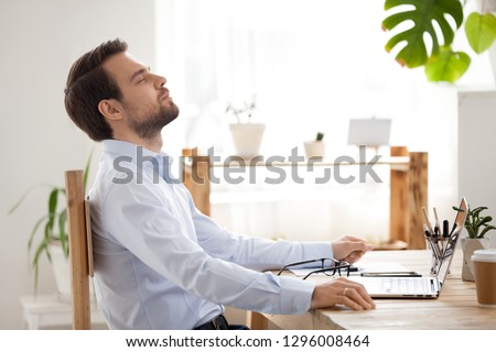 Satisfied calm businessman taking break to relax finished work sitting at desk enjoying stress free job breathing fresh air, happy executive manager resting at workplace dreaming in quiet office