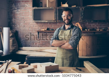 Satisfied cheerful joyful smiling with stylish hairdo bearded wearing apron woodmaster is standing near desktop with crossed arms in his workshop, workstation