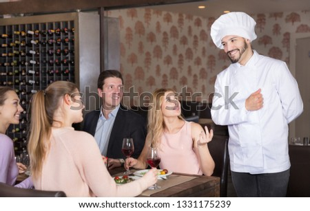 Smiling chef serving customers in restaurant Images and