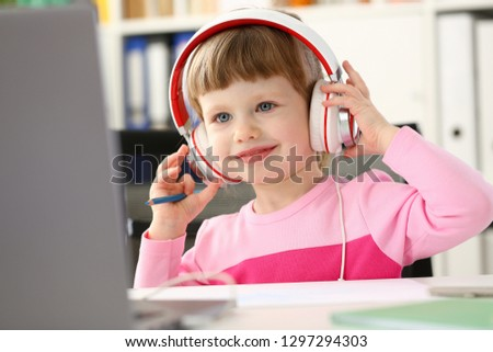 Satisfied child in headphones sitting at home office table and looking into camera portrait. Makes orders in online store with home delivery concept management game play early development