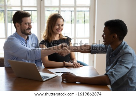 Satisfied clients married couple making successful deal with broker or realtor, happy family purchasing new house, taking loan or mortgage, smiling man husband shaking hand of manager at meeting