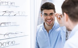 Satisfied Customer. Over the shoulder view of happy young male client wearing new glasses, looking in the mirror standing near rack and showcase with eyewear. Smiling man trying on spectacles