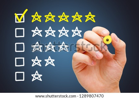 Satisfied customer putting yellow check mark with marker on five star in evaluation form.  #1289807470