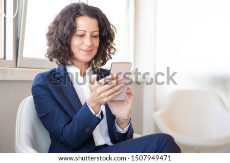 Satisfied customer using online mobile app. Business woman sitting in armchair, using mobile phone, looking at screen and smiling. Digital technology concept Foto d'archivio ©