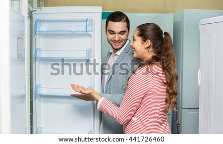 Satisfied customers looking at large fridges in domestic appliances section #441726460