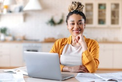 Satisfied good looking young African American stylish woman, freelancer, student or real estate agent, sitting at her desk at home office, looking at the camera and smiling pleasantly
