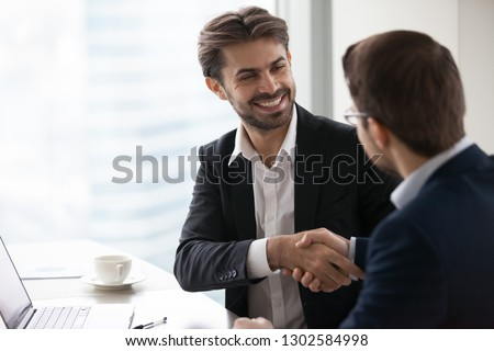 Satisfied happy businessman in suit handshake business partner making deal thanking for teamwork, executive manager and client shake hands after successful negotiations, hiring, forming partnership