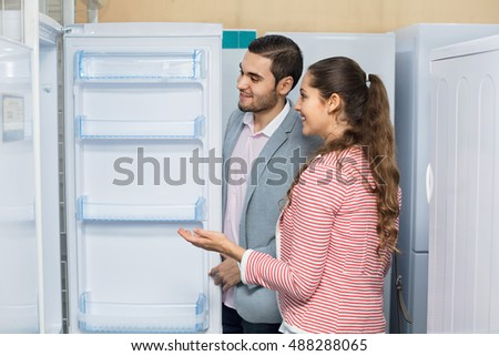 Satisfied happy customers looking at large fridges in domestic appliances section #488288065