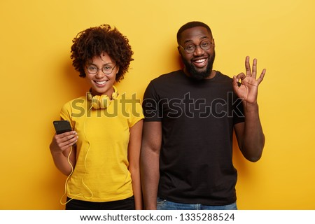 Satisfied happy hipsters with dark skin, spend leisure time with modern technologies, holds smart phone, listen music in headphones, make okay gesture, agree to go on party, like new audio track