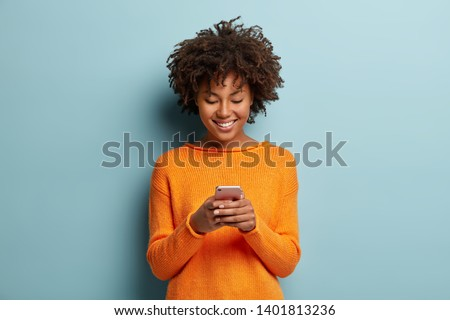 Satisfied hipster girl with Afro haircut, types text message on cell phone, enjoys online communication, types feedback, wears orange jumper, isolated on blue studio wall. Technology concept