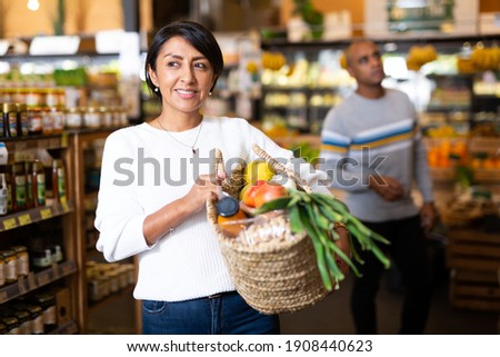 Satisfied hispanic woman with wicker bag filled with fresh food goods bought in supermarket Stock foto ©