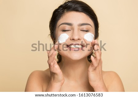 Satisfied indian lady applying cleansing foam luxury cream on cheeks, grooming herself head shot close up portrait. Joyful female client using recommended skin treatment isolated on beige background.